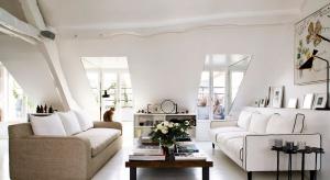 Lekki, pełen światła i elegancki - taki jest ten pokój dzienny w znajdującym się na poddaszu paryskiej kamienicy mieszkaniu.