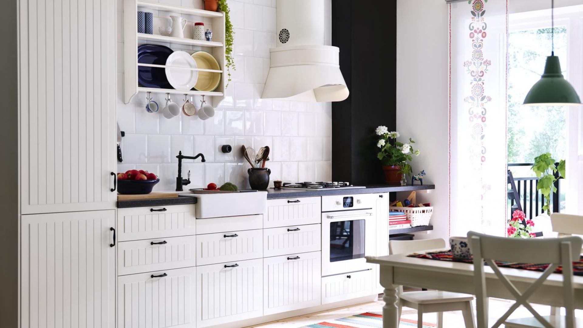 Skandynawska zabudowa na jedną ścianę. Pionowe frezowania zdobią fronty, a dolną zabudowę wieńczy ciemny blat. Fot. IKEA.