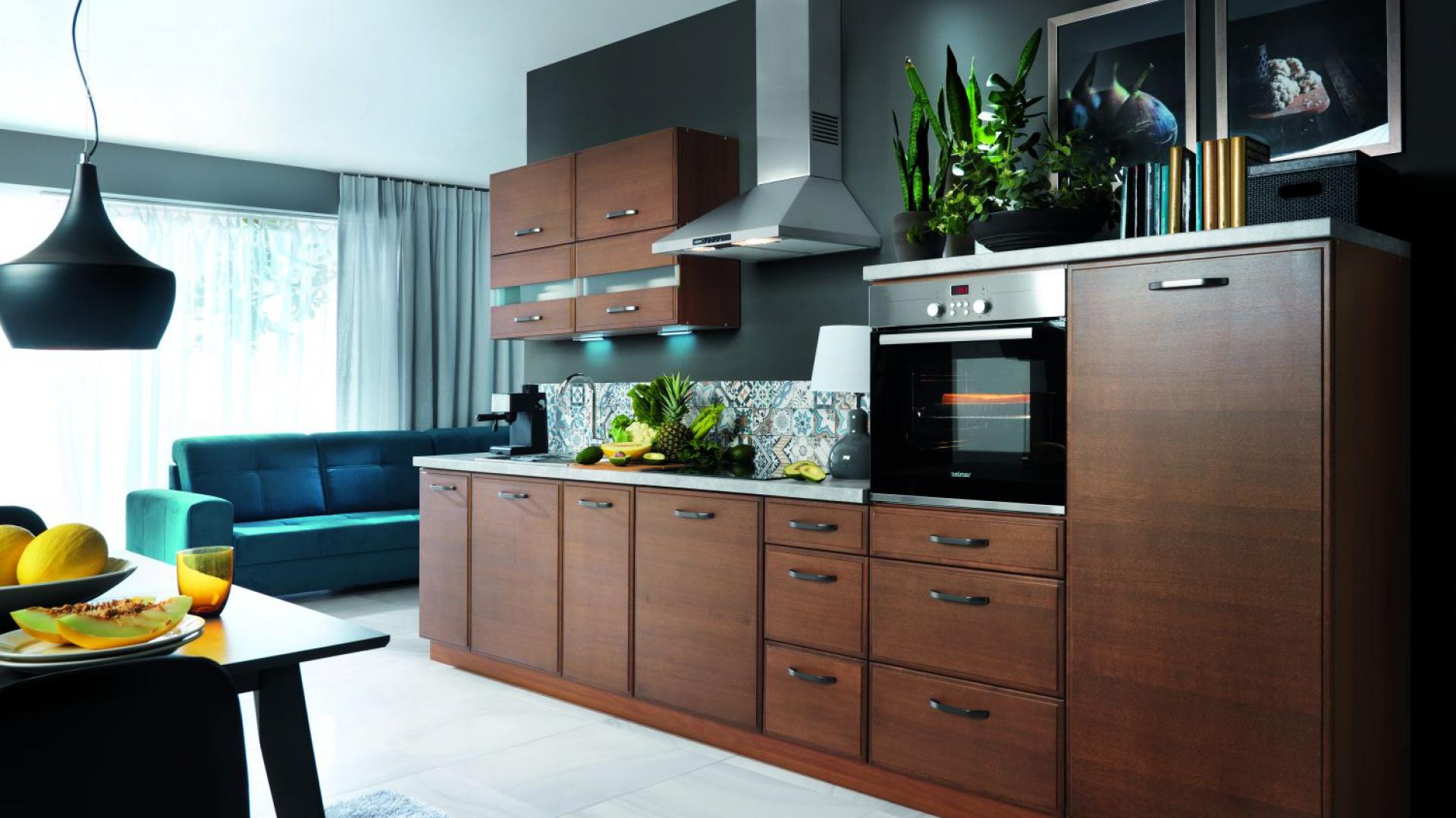 Ciemne wybarwienie drewna sprawia, że ten aneks kuchenny może wręcz udawać meblościankę w salonie. Fot. Black Red White, model Aplaus.