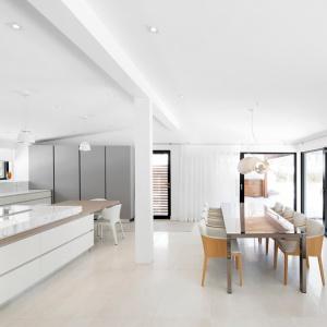 Kuchnia i jadalnia stanowią jedno, wspólne pomieszczenie. Przestrzeń przygotowywania posiłków stanowi duża wyspa z pięknym, kamiennym blatem. Projekt: Architecture Open Form. Fot. Adrien Williams.