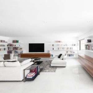 Oszczędna aranżacja salonu pozwoliła na wykorzystanie praktycznych, otwartych półek jako biblioteczki. Mimo dużej ilości książek, nie tworzą one wrażenia nieporządku w pokoju dziennym. Projekt: Architecture Open Form. Fot. Adrien Williams.