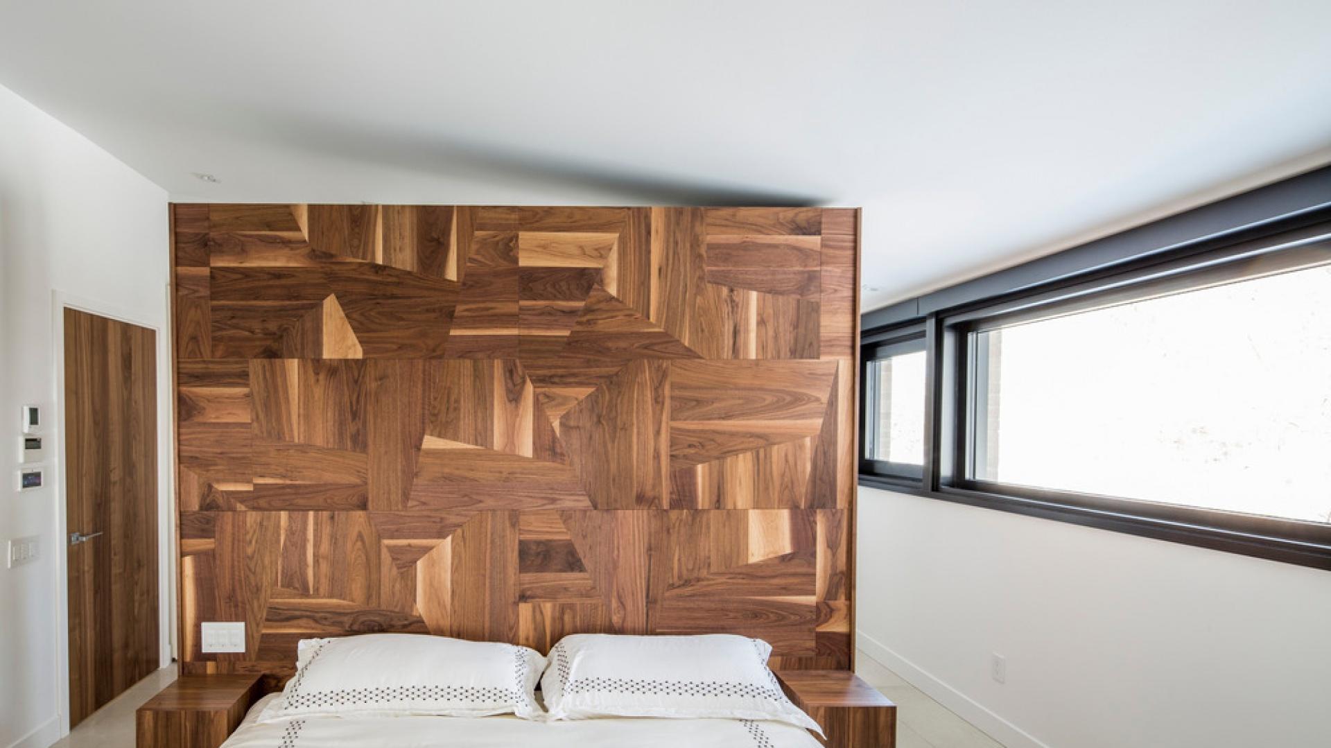 Geometryczną mozaikę z drewna możemy zobaczyć w sypialni. Oryginalny zagłówek łóżka wygląda niczym kubistyczne dzieło sztuki. Projekt: Architecture Open Form. Fot. Adrien Williams.