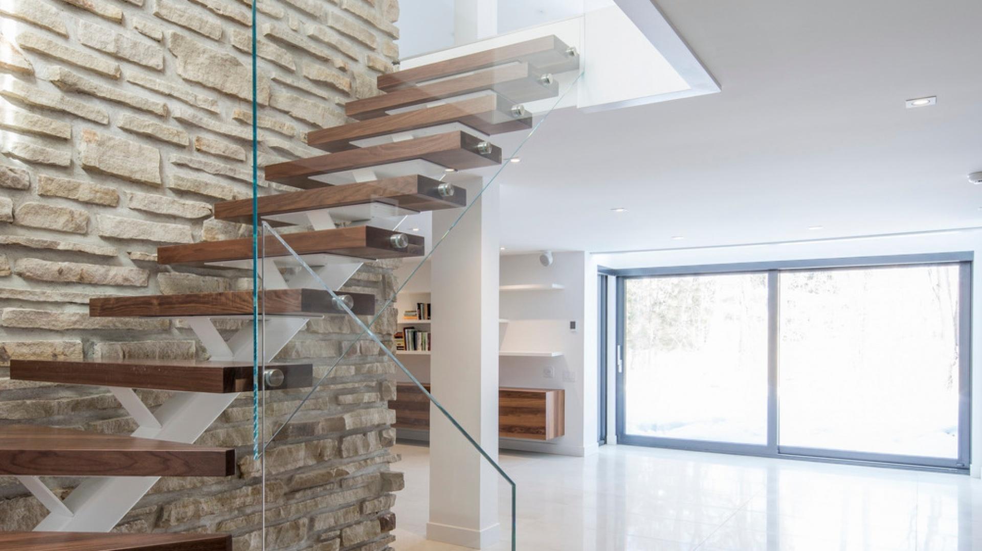Klatka schodowa jest najlepszym odzwierciedleniem stylistyki, panującej w całym domu. Szklana balustrada i wiszące stopnie nawiązują do nowoczesnej architektury, a kamień na ścianie i drewno na stopniach do tradycji. Projekt: Architecture Open Form. Fot. Adrien Williams.
