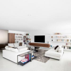 Salon urządzono w jasnych, stonowanych barwach. Dominację bieli równoważą elementy drewniane i w kolorach ziemi. Projekt: Architecture Open Form. Fot. Adrien Williams.