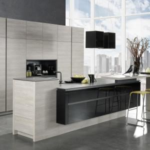 Zabudowę kuchenną zdobi okleina drewniana w popielatym odcieniu drewna. Wyspę tworzy asymetryczna bryła wykończona w dwóch kolorach. Czerń w wysokim połysku efektownie uzupełnia szarawy odcień drewna. Fot. Rational, kuchnia Tio Glass.