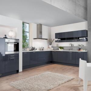 Granatowoszare fronty idealnie harmonizują z betonową ścianę. Z kolei kontrast faktur sprawia, że kuchnia nabiera dynamiki. Fot. Wellmann, meble z programu Calla.