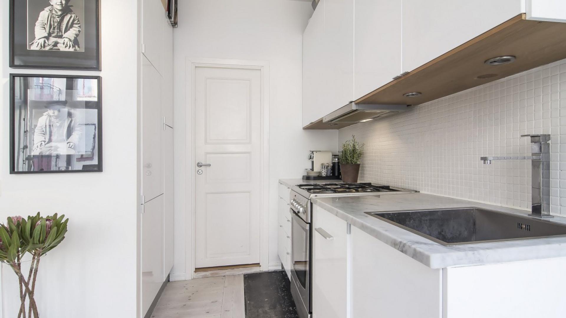 W niewielkim aneksie kuchennym sprawdziły się meble montowane na jednej ścianie. Fot. SvenskFast.se