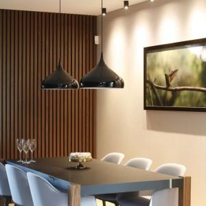 Dwie wiszące lampy o opływowym, subtelnym kształcie, czarnej intensywnej barwie i wykończeniu w połysku towarzyszą mniejszym, czarnym punkcikom zamontowanym w suficie. Projekt: Jan Sikora. Fot. Bartosz Jarosz.