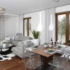 Dwie smukłe białe lampy o opływowych kształtach subtelnie górują nad drewnianym stołem i metalowymi krzesłami. Projekt: Piotr Stanisz. Fot. Bartosz Jarosz.
