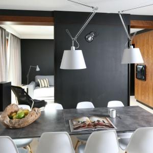 Dwie efektowne lampy górują dumnie nad betonowym blatem stołu, zawieszone na metalowych wysięgnikach. Czarna ściana sprawia, że są bardzo mocno wyeksponowane i przyciągają wzrok. Projekt: Kasia i Michał Dudko. Fot. Bartosz Jarosz.