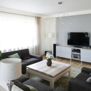 Szara ściana z telewizorem podkreśla nowoczesny charakter tego przytulnego wnętrza. Projekt: Marta Kruk. Fot. Bartosz Jarosz.