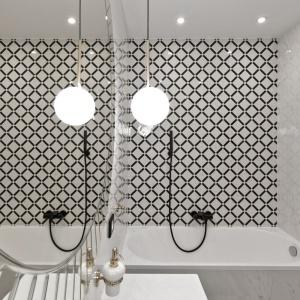 Monochromatyczna kolorystyka łazienki nie prezentuje się nudno, a to za sprawą wzorów zdobiących ścianę nad wanną. Projekt: Indre Sunklodiene. Fot. Leon Garbačauskas.