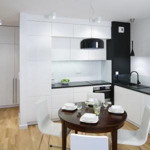 Aneks kuchenny na dwie ściany urządzono w bieli i czerni. Fronty i cokoły szafek są białe, ale wieńczy je czarny blat. Projekt: Ewa Para. Fot. Bartosz Jarosz.