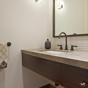 W drugiej łazience bardziej zaakcentowano ciemne kolory. Ciekawie prezentuje się antracytowa rama lustra harmonizująca z baterią umywalkową. Projekt: Studio Vara. Fot. Bruce Damonte.