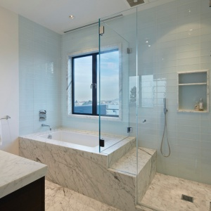 W łazience naturalny marmur zestawiono z dużymi taflami szkła. Wanna sąsiaduje w ciekawy sposób ze strefą prysznica. Projekt: Studio Vara. Fot. Bruce Damonte.