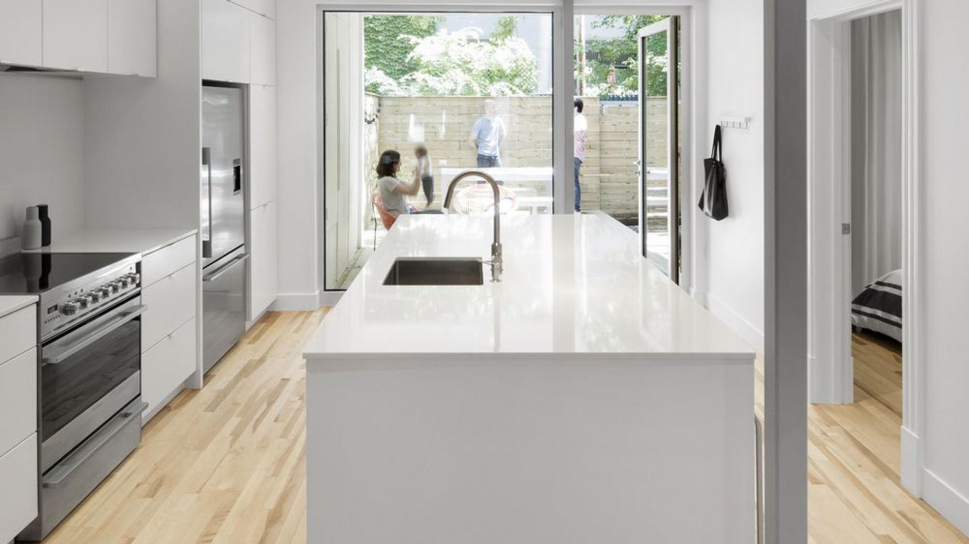 Kuchnię od kameralnego patio oddzielają duże, panoramiczne przeszklenia. Projekt: Bourgeois / Lechasseur Architects. Fot. Adrien Williams.