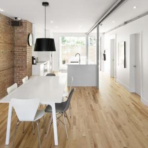 Długa ściana wykończona czerwoną cegłą i drewniana posadzka na podłodze w całej strefie dziennej spajają ją wizualnie. Projekt: Bourgeois / Lechasseur Architects. Fot. Adrien Williams.