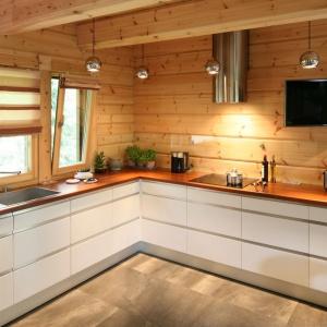 Kontrast pomiędzy ścianą z drewnianych bali a nowoczesną zabudową kuchenną i okapem dodatkowo podkreśla telewizor zamontowany nad blatem kuchennym. Projekt: Tomasz Motylewski i Marek Bernatowicz. Fot. Bartosz Jarosz.