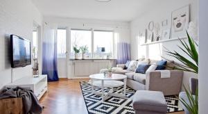 Dużo bieli, drewniana podłoga oraz szare i błękitne detale. Tak urządzono to urokliwe mieszkanie, które zachwyca optymistycznym wnętrzem.
