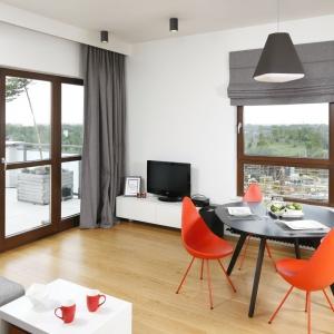 Czerwone designerskie krzesła to element strefy dziennej tego mieszkania, który zdecydowanie nadaje ton całej aranżacji. Połączenie salonu z małą jadalnią pozwoliło wyeksponować meble w intensywnym kolorze i osiągnąć ten spektakularny efekt. Projekt: Małgorzata Łyszczarz. Fot. Bartosz Jarosz.