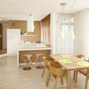 Ultra-nowoczesne mieszkanie z równie nowoczesną jadalnią. Wkomponowana w przestrzeń pomiędzy kuchnią z półwyspem a salonem, utrzymana w nowoczesnych, prostych formach i kolorze drewna stanowi harmonijny element aranżacji otwartej strefy dziennej. Projekt: Marcin Brzostek. Fot. Bartosz Jarosz.