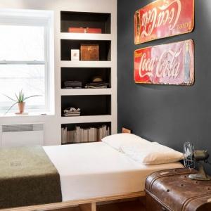 Podobnymi wnękami zabudowano okno w sypialni. Tutaj wzrok najbardziej przyciągają jednak vintage'owe emaliowane plakietki na ścianie. Projekt: MARK+VIVI. Fot. Adrien Williams.
