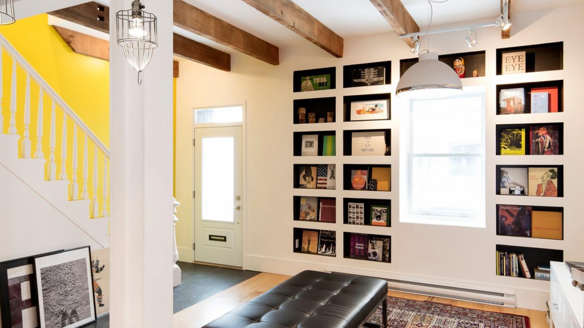 W salonie w zabudowę ścienną wkomponowane nisze-półki, na których mogą stanąć książki bądź dekoracje. Projekt: MARK+VIVI. Fot. Adrien Williams.