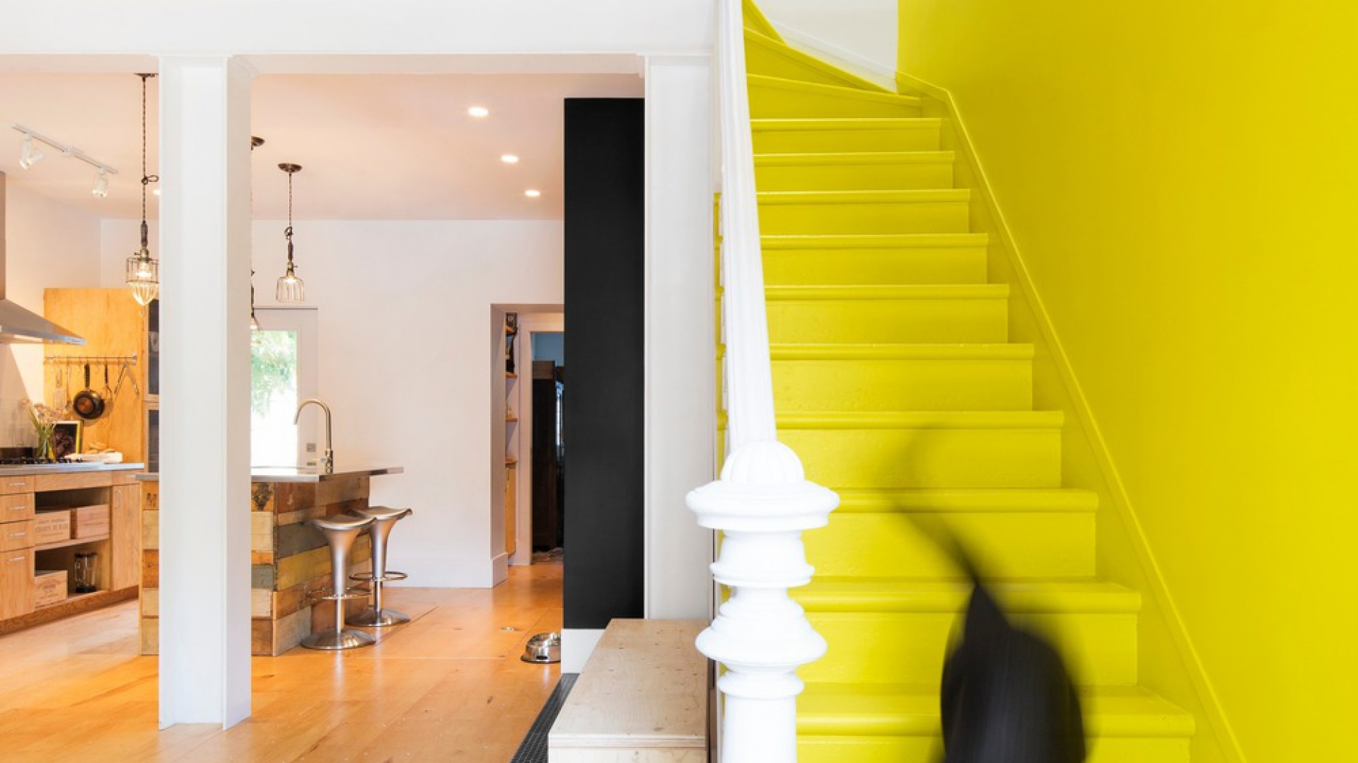 Oprócz intensywnego żółtego koloru, klatkę schodową od reszty strefy dziennej oddziela również oryginalna, czarno-biała posadzka. Projekt: MARK+VIVI. Fot. Adrien Williams.