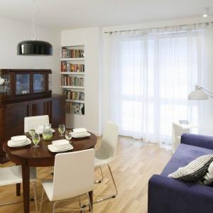 Niebieska sofa w pokoju dziennym stanowi mocny akcent we wnętrzu. Kontrast dla zabytkowego kredensu stanowią półki na książki umieszczone w ściennej wnęce. Dzięki takiemu połączeniu wystrój salonu ma eklektyczny charakter. Projekt: Ewa Para. Fot. Bartosz Jarosz.