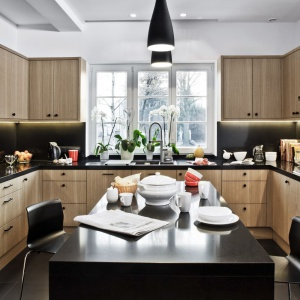 Naturalny fornir dębowy pokrywa fronty zabudowy kuchennej. Z kolei pogrubiony blat z konglomeratu kwarcowego jest czarny i koresponduje z dekoracyjnymi uchwytami w tym samym kolorze. Fot. Zajc Kuchnie, model Z5.