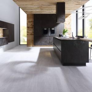 Wyjątkowa kuchnia, w której zarówno blat, jak i fronty zostały wykonane ze spieków kwarcowych. Ceramiczna powierzchnia w ciemnym kolorze tworzy piękną kompozycję z jasnym drewnem. Fot. Alno, meble z programu Alnostar Cera.
