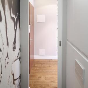 Bardzo wąska łazienka ma niestandardowe drzwi: wysokie i przesuwne. Dzięki temu nie utrudniają przechodzenia. Fot. Bartosz Jarosz.