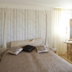 Tapeta z motywem leśnych brzózek wprowadzi do wnętrza sypialni naturalny klimat. Doskonale komponuje się z bielą ścian. Projekt: Marta Kruk. Fot. Bartosz Jarosz.