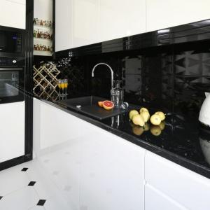 Z białą zabudową kuchenną efektownie kontrastują czarne płytki ceramiczne z delikatną, geometryczną fakturą 3D. Projekt: Katarzyna Mikulska-Sękalska. Fot. Bartosz Jarosz.