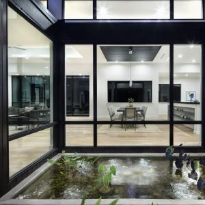 Duże okna zespalają wnętrze domu z równie efektownym otoczeniem. Projekt: Clark | Richardson Architects. Fot. Paul Finkel.