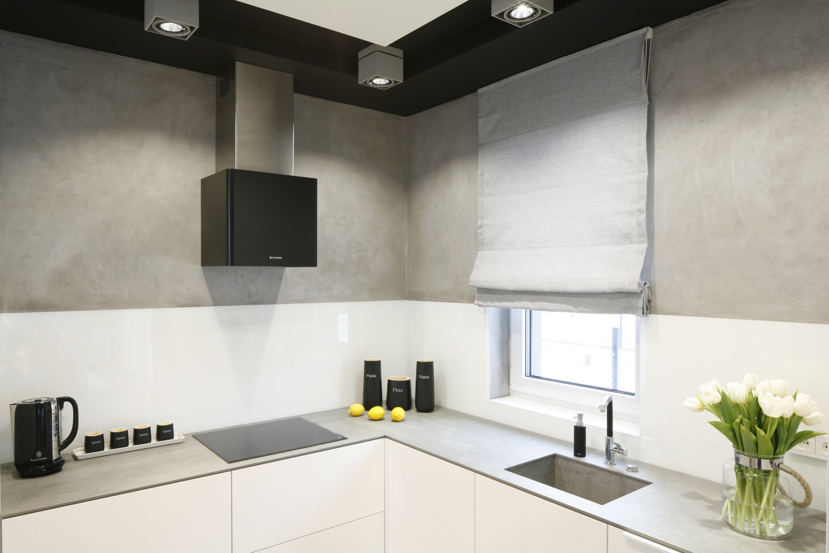Ścianę nad blatem przekryto lakierowanym białym szkłem, a powierzchnię powyżej wykończono betonowym tynkiem. Projekt: Karolina Stanek-Szadujko i Łukasz Szadujko. Fot. Bartosz Jarosz.