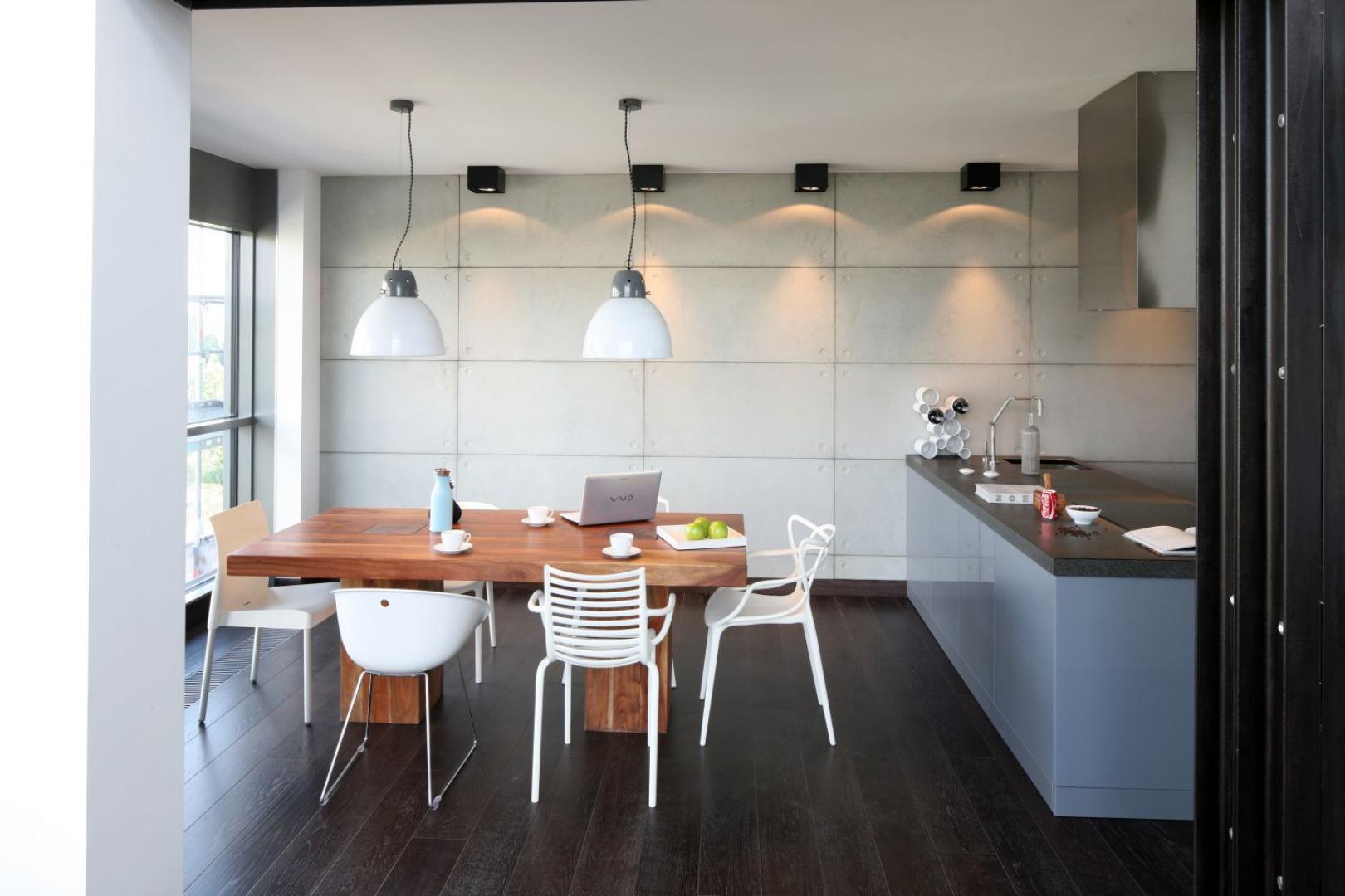Prostokątne betonowe płyty rozciągają się wzdłuż kuchni i jadalni, spajając ze sobą wizualnie obie przestrzenie. Projekt: Justyna Smolec. Fot. Bartosz Jarosz.