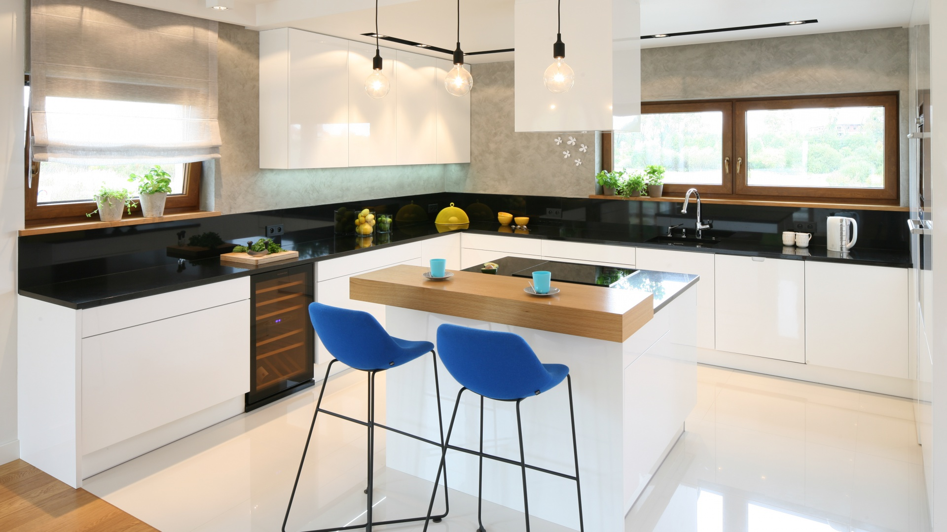 Tynk imitujący beton znalazł się również na ścianie w tej przestronnej białej kuchni. Nadaje on nowoczesnej, połyskującej zabudowie nieco surowy charakter. Projekt: Małgorzata Galewska. Fot. Bartosz Jarosz.
