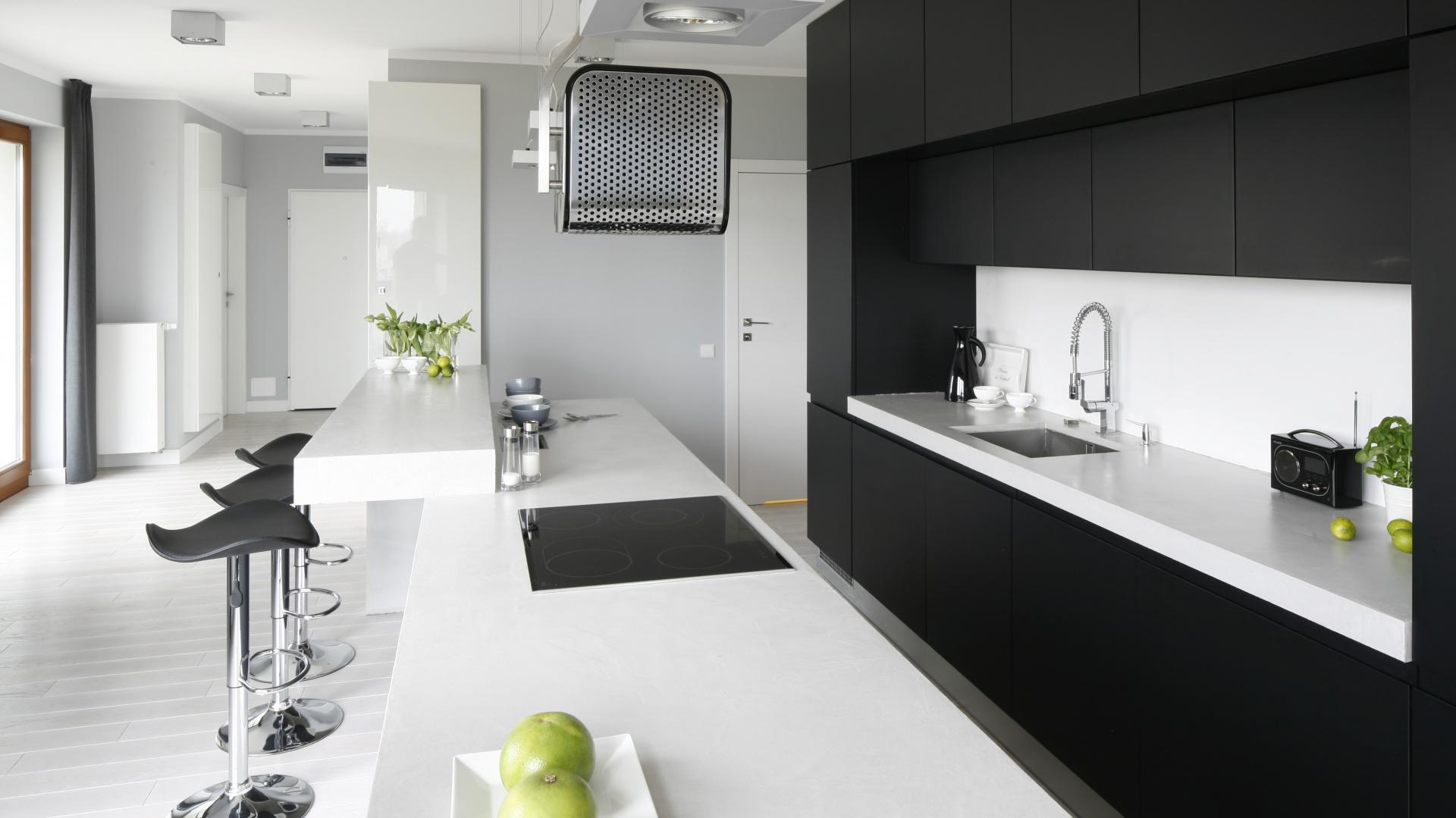 Betonowy jest również kuchenny blat. Jasnym kolorem efektownie kontrastuje z matowymi, czarnymi frontami zabudowy kuchennej. Projekt: Maciejka Peszyńska-Drews. Fot. Bartosz Jarosz.