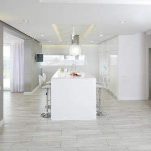 Przestronna biała kuchnia ze ścianami wykończonymi betonowym tynkiem, na którym odciśnięto linie imitujące granice betonowych płyt. Projekt: Dominik Respondek. Fot. Bartosz Jarosz.