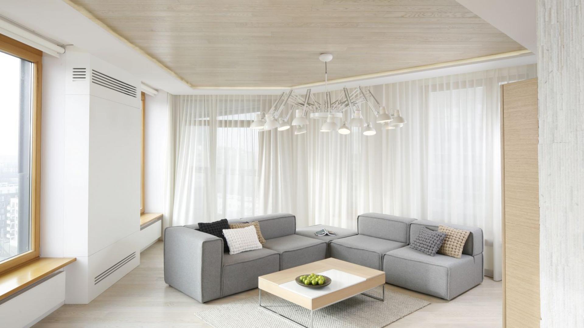 Przestronny salon urządzono w stylu skandynawskim. Stąd jasna paleta barw oraz drewno w chłodnym wybarwieniu. Projekt: Maciej Brzostek. Fot. Bartosz Jarosz.