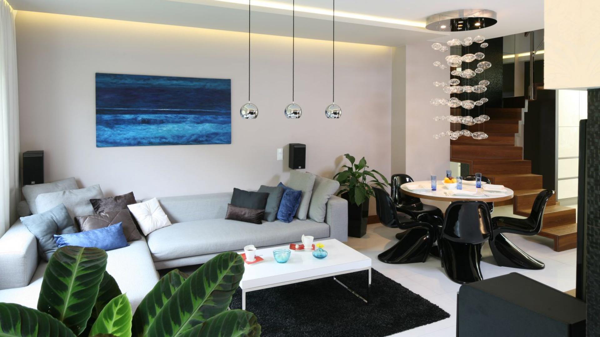 Otwarta przestrzeń na parterze zaprojektowana jest w spójnej kolorystyce bieli, szarości, czerni i brązu. Turkusowe dodatki, kojarzące się z błękitem oceanu i wspaniałym australijskim niebem, doskonale ją ożywiają. Projekt: Chantal Springer. Fot. Bartosz Jarosz.