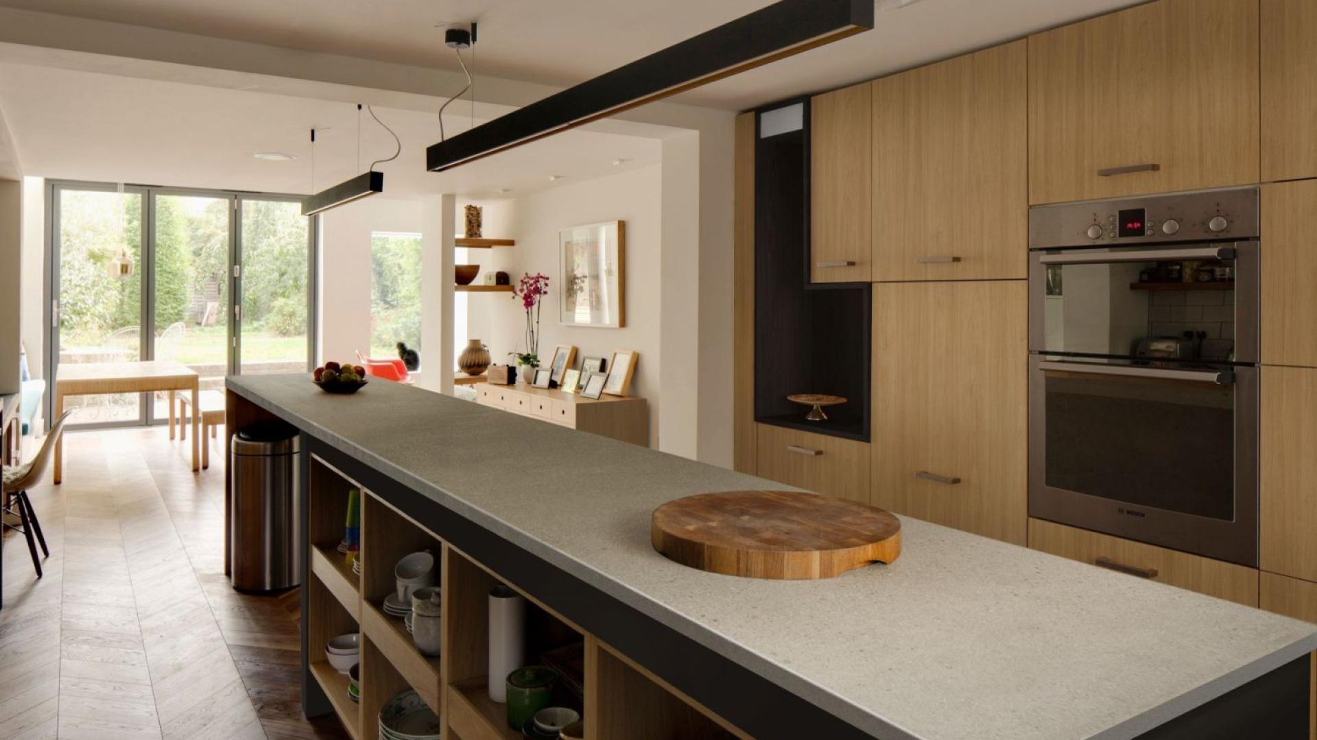 Długą, pojemną wyspę kuchenną z licznymi półkami pokrywa szary blat z laminatu. Fot. Pfleiderer, blat laminowany Snowland.