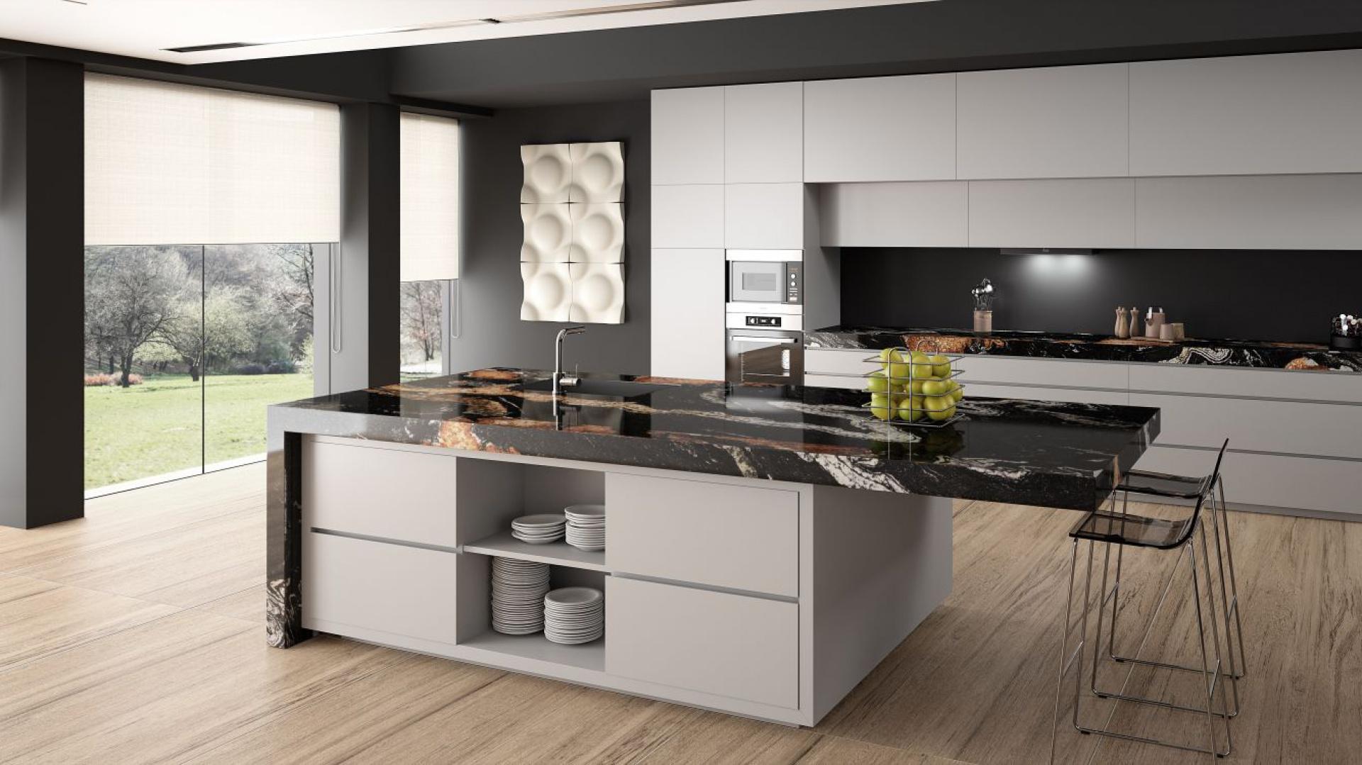 Kamienny blat sprawdzi się nie tylko w klasycznych kuchniach, wspaniale harmonizuje również z nowoczesną zabudową, nadając jej szyk i elegancję. Tutaj w wersji blisko 10-centymetrowej został nałożony na dolną zabudowę oraz wyspę kuchenną, wychodząc poza jej obrys i pełniąc również funkcję baru. Fot. Cosentino, blat Sensa by Cosentino Orinoco.