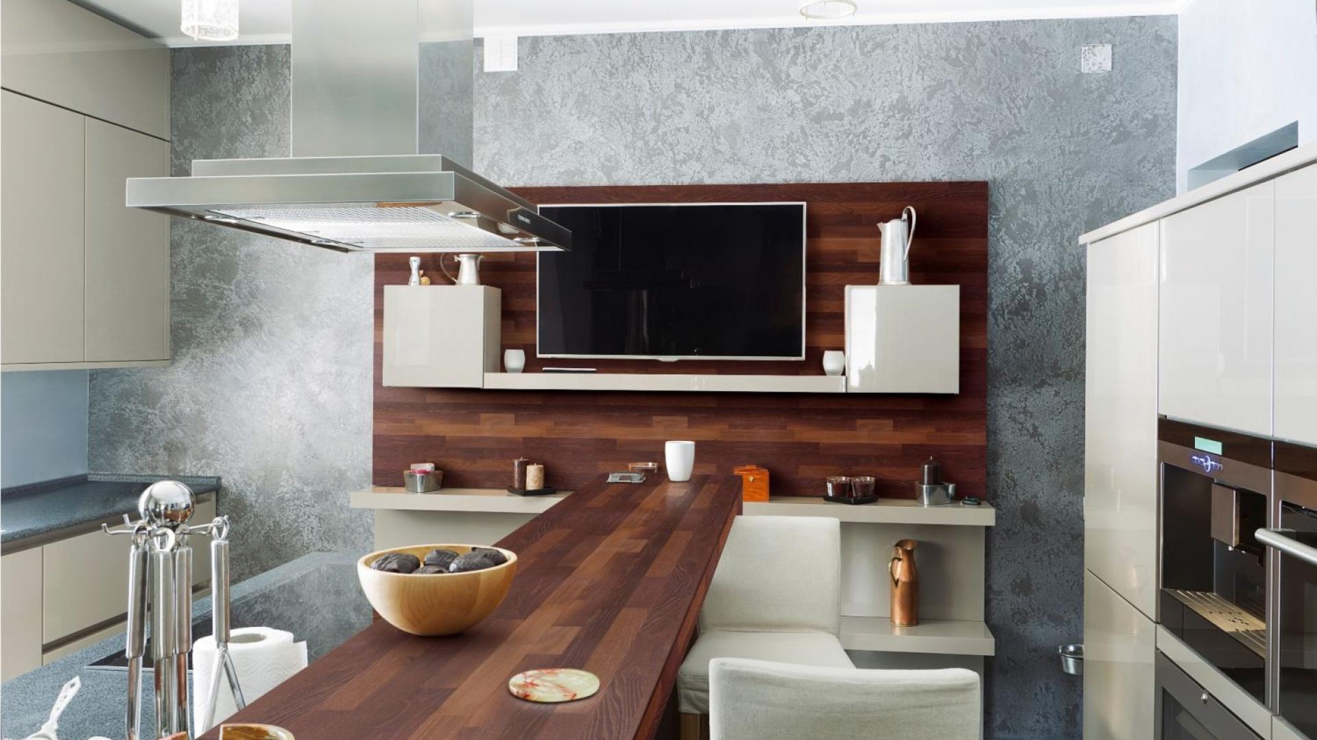 Piękny blat wykonany z naturalnego drewna akacjowego, parzonego i klejonego, aby uzyskać większą trwałość materiału. Głęboka barwa pięknie kontrastuje z jasnymi odcieniami zabudowy kuchennej i ściany w salonie. Fot. DLH.