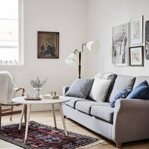 Tradycyjny pleciony dywan wspólnie z licznymi poduszkami dekoracyjnymi buduje w głównym pokoju przytulną atmosferę. Fot. Janne Olander/Stadshem.se.