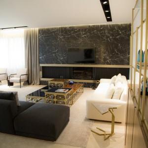 Intrygującym elementem umeblowania pomieszczenia są różnej wysokości stoliki kawowe, układające się w asymetryczną ławę. Projekt: Ronald Helou Design. Fot. Rudy Bouchebel.