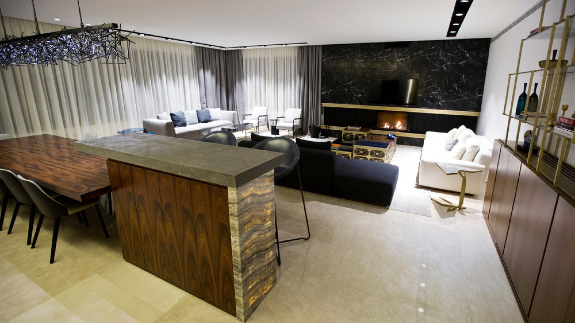 Chcąc zaoszczędzić przestrzeń, architekci postanowili jadalnię połączyć z wyspą, zestawiając wysoki bar z długim stołem jadalnianym. Projekt: Ronald Helou Design. Fot. Rudy Bouchebel.