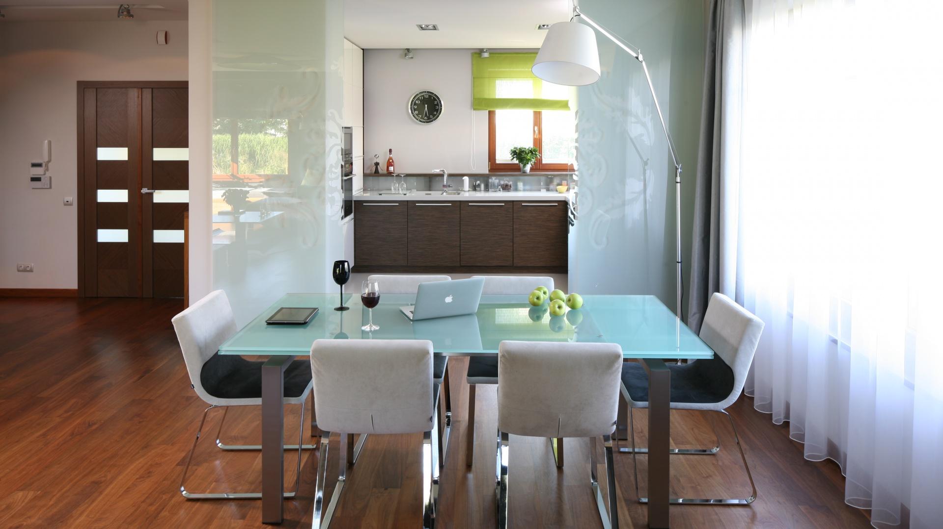 Umiejscowioną w obszernym kubiku kuchnię, dzięki szklanym przesuwnym drzwiom można w każdej chwili całkowicie zamknąć. Projekt Magdalena Konopka, Maciej Konopka. Fot. Bartosz Jarosz.