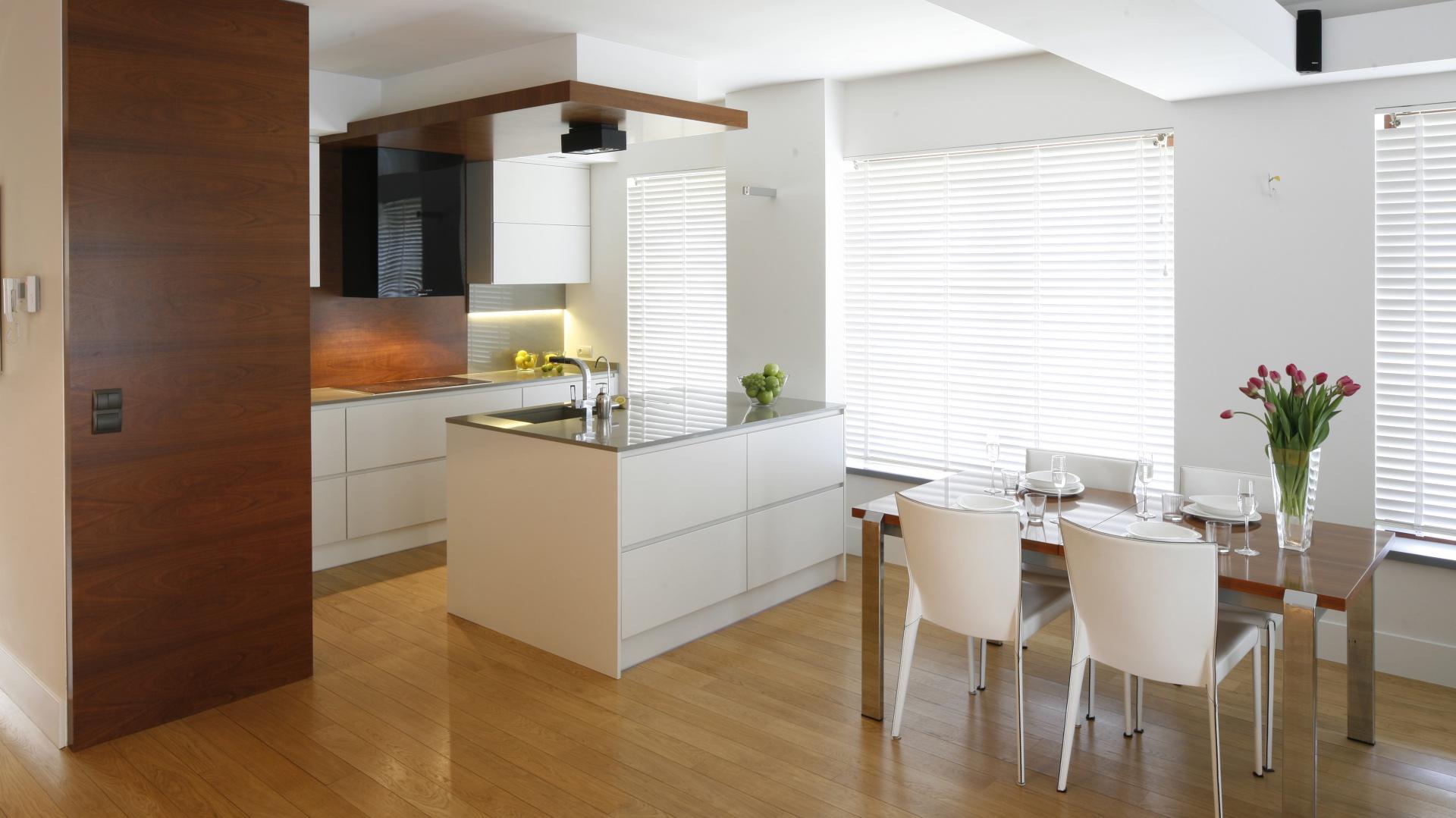 Otwarta na salon kuchnia urządzona została w tej samej bazie kolorystycznej co reszta domu. Ociepla ją drewno w postaci forniru. Projekt: Kamila Paszkiewicz. Fot. Bartosz Jarosz.